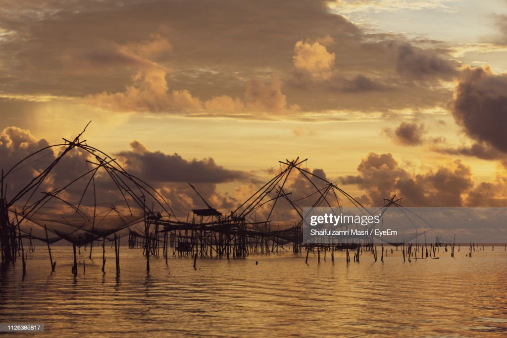 Silhouette Fishing Nets On Sea Against Cloudy Sky During Sunset : Stock Photo