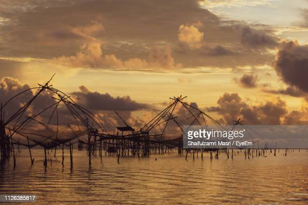 silhouette fishing nets on sea against cloudy sky during sunset - shaifulzamri 個照片及圖片檔