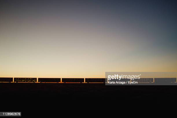 silhouette freight train against clear sky during sunset - 貨物列車 ストックフォトと画像