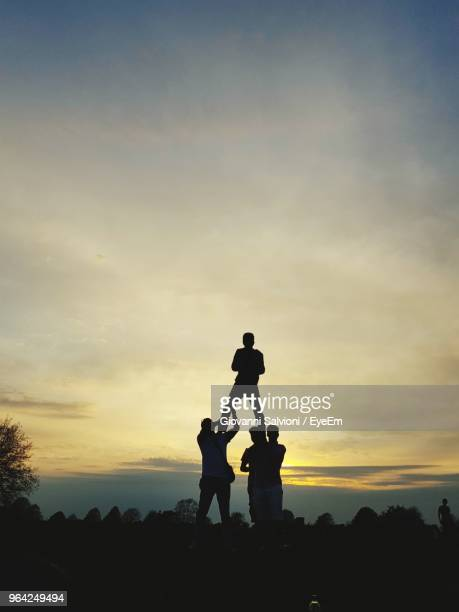 silhouette friends forming human pyramid against sky during sunset - pyramid stock pictures, royalty-free photos & images
