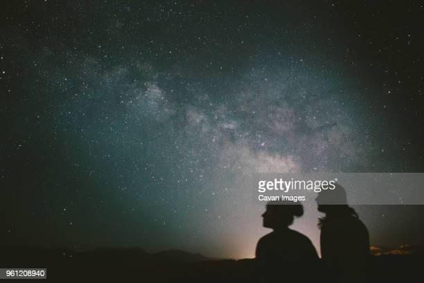 silhouette friends looking at stars during night - astronomie stock-fotos und bilder