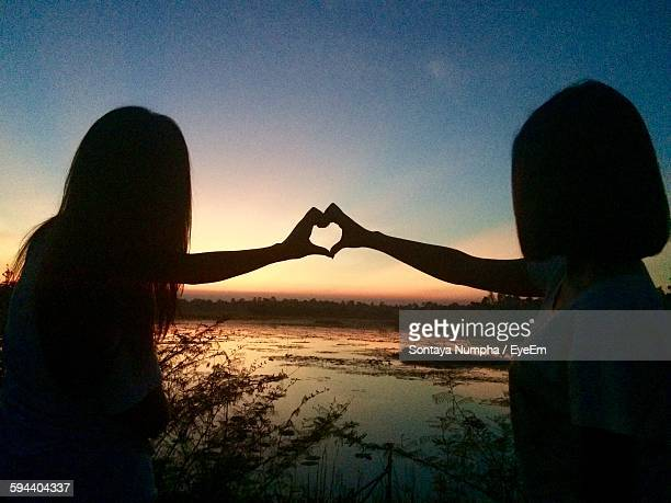 Silhouette Friends Making Heart Shape By River Against Sky During Sunset