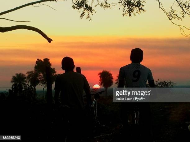Silhouette Friends On Landscape Against Sky During Sunset