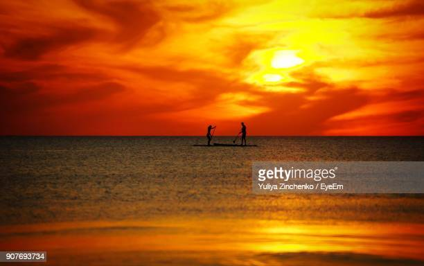 silhouette friends paddleboarding in sea against sky during sunset - zinchenko stock pictures, royalty-free photos & images