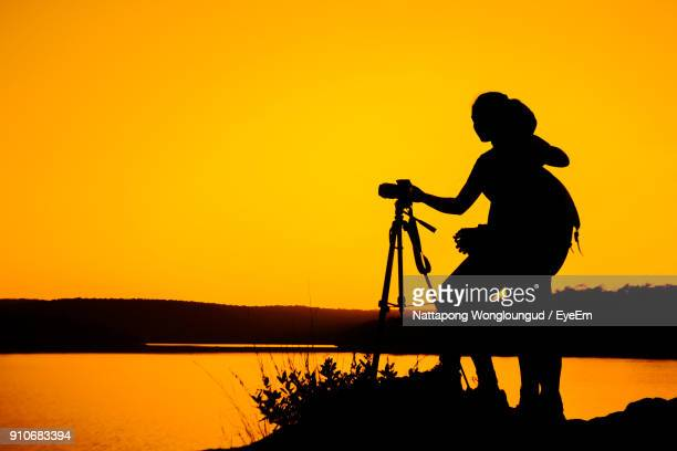 silhouette friends photographing while standing by lake against clear sky during sunset - camera girls stock photos and pictures
