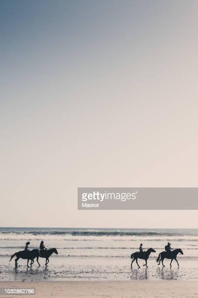 silhouette friends riding horses at beach against clear sky during sunset - waterlijn stockfoto's en -beelden