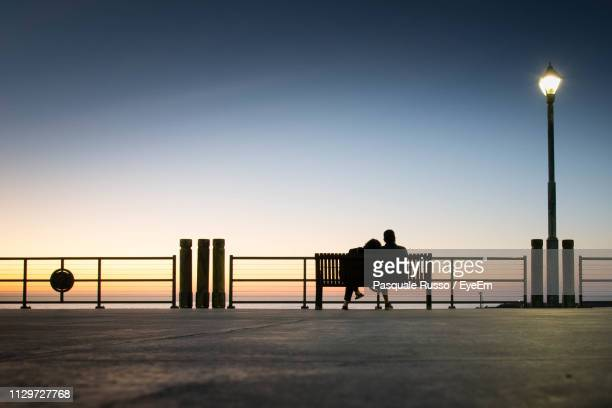 silhouette friends sitting on bench against clear sky during sunset - ベンチ ストックフォトと画像