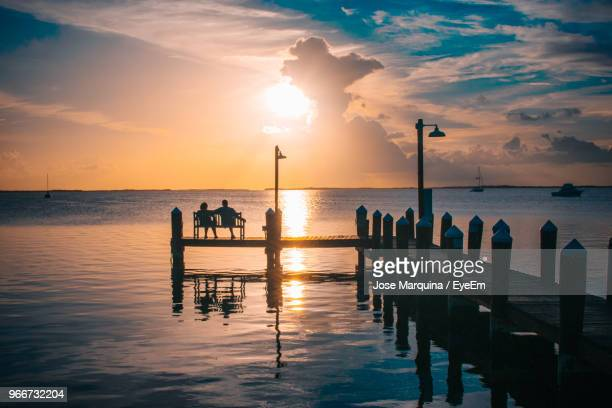 silhouette friends sitting on bench at pier over sea against sky during sunset - florida keys stock pictures, royalty-free photos & images