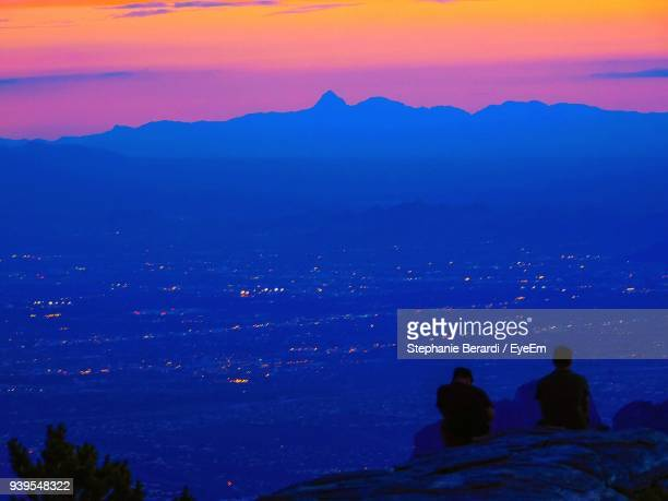 Silhouette Friends Sitting On Cliff Against Sky During Sunset