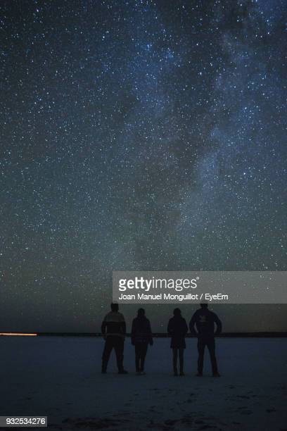 Silhouette Friends Standing Against Star Field At Night
