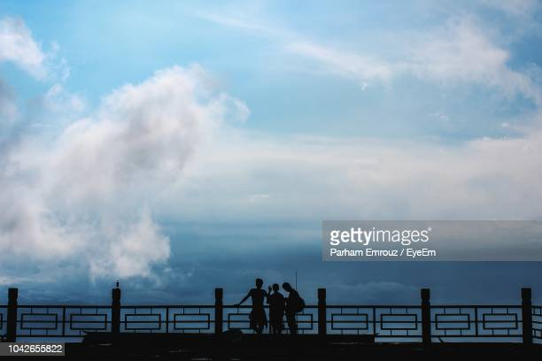 silhouette friends standing on bridge against cloudy sky - parham emrouz stock pictures, royalty-free photos & images