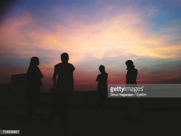 Silhouette Friends Standing On Building Terrace Against Sky During Sunset