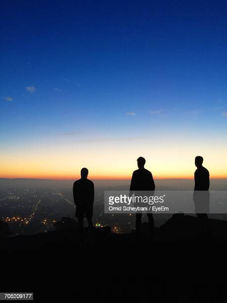Silhouette Friends Standing On Mountain By Illuminated City Against Blue Sky During Sunset