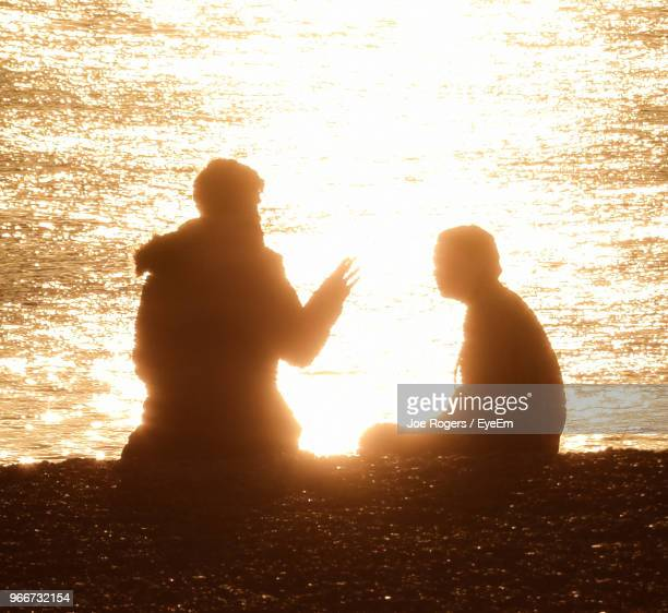 silhouette friends talking while sitting at beach during sunset - 膝から上の構図 ストックフォトと画像