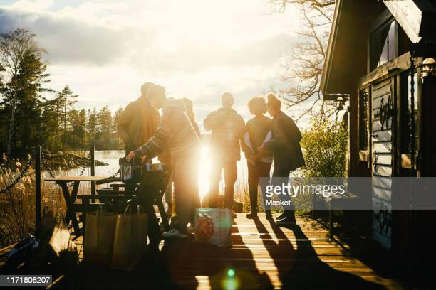 silhouette friends talking while standing outside cottage in front of lake during sunset - milleniumgeneratie stockfoto's en -beelden