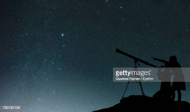 silhouette friends using telescope against star field at night - 6 point star stock pictures, royalty-free photos & images