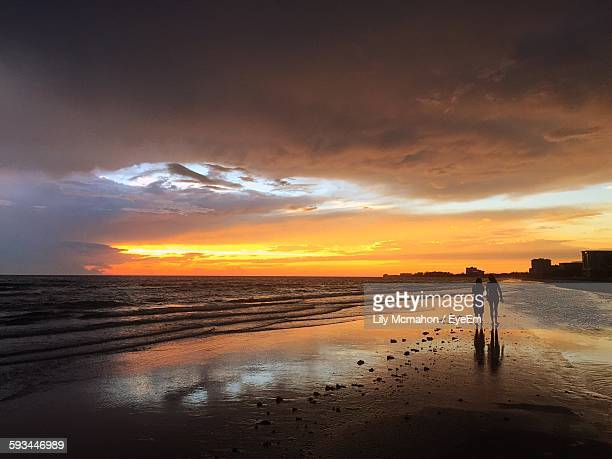 silhouette friends walking on beach against cloudy sky during sunset - siesta key stock pictures, royalty-free photos & images