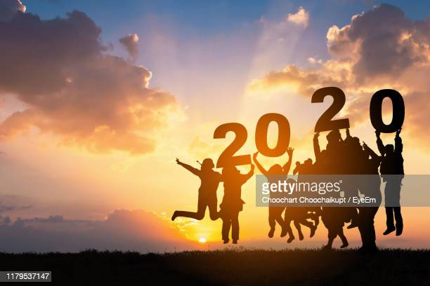 silhouette friends with 2020 sign jumping on land during sunset - 2020 stock pictures, royalty-free photos & images