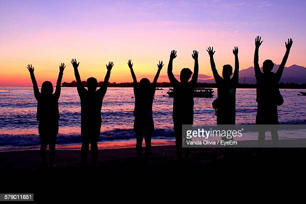 Silhouette Friends With Arms Raised On Shore During Sunset