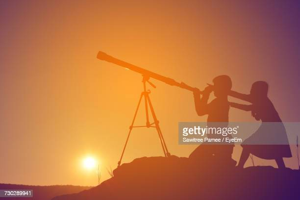 Silhouette Girl And Boy Looking Through Telescope On Hill Against Clear Sky During Sunset