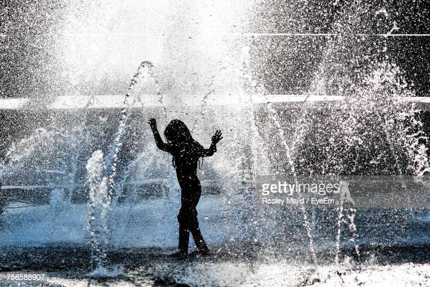 silhouette girl enjoying amidst fountain at park - putrajaya stock photos and pictures