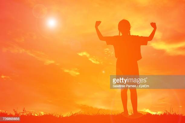 silhouette girl flexing muscles while standing on field against orange sky - girl power stock photos and pictures