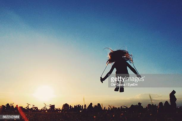Silhouette Girl Jumping In Park Against Clear Sky At Sunset