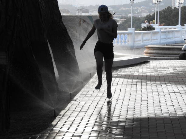 Silhouette Girl Jumping On Footpath In City