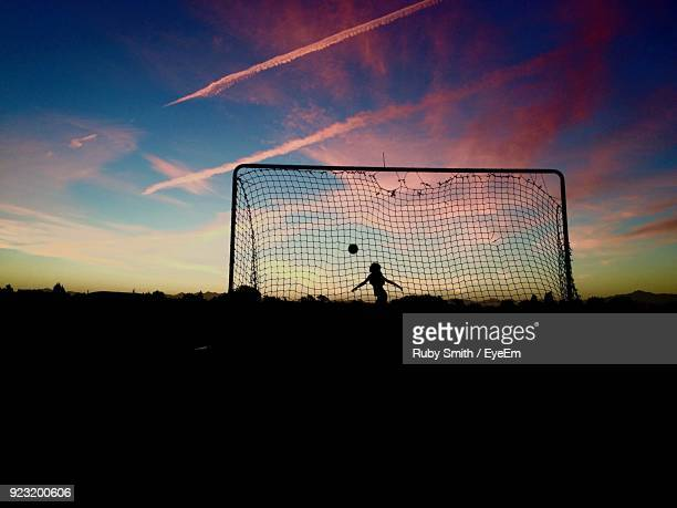 Silhouette Girl Playing With Ball On Field Against Sky During Sunset