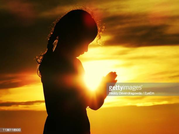 silhouette girl standing against sky during sunset - innocence stock pictures, royalty-free photos & images