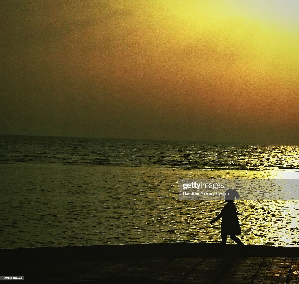 Silhouette Girl Walking On Beach During Sunset : Stock Photo