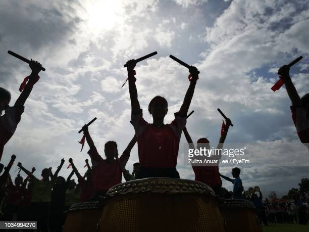 silhouette girls at parade while banging drums against sky - percussion instrument stock photos and pictures