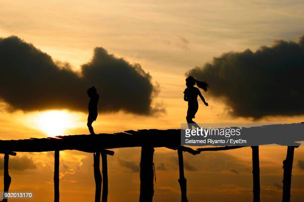 Silhouette Girls On Footbridge Against Sky During Sunset