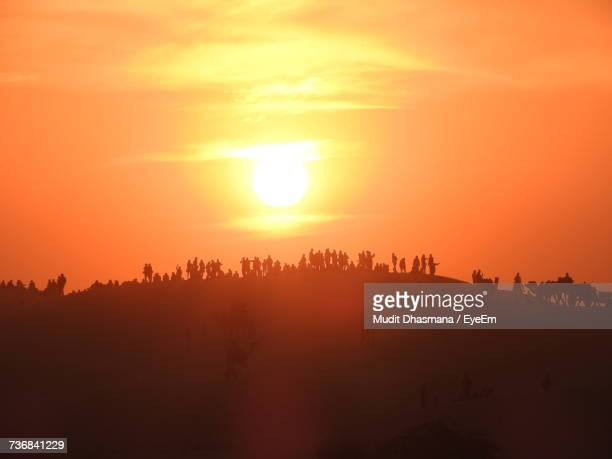 silhouette group of people in desert against orange sky - heat haze stock pictures, royalty-free photos & images