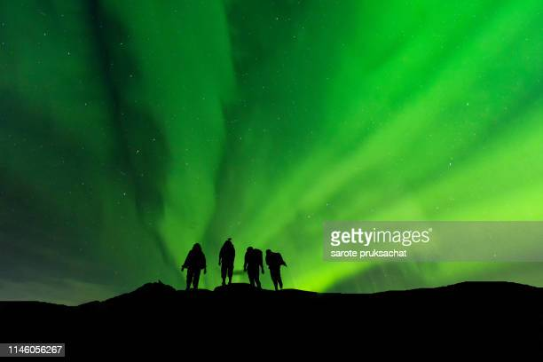 silhouette group standing on top of peak mountain and aurora light . - space and astronomy stock pictures, royalty-free photos & images