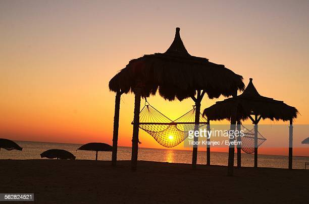 Silhouette Hammock In Thatched Roof Hut Against Sunset Sky In Marsa Alam Resort