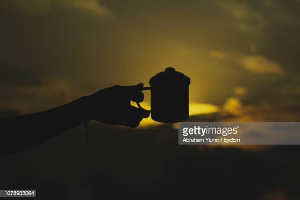 Silhouette Hand Holding Against Sky During Sunset