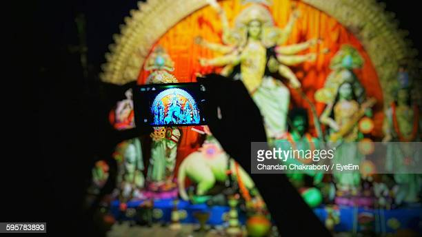 Silhouette Hands Of Person Photographing Through Smart Phone Durga At Temple