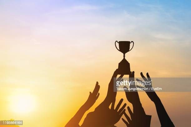 silhouette hands reaching trophy against sky during sunset - trophy stock pictures, royalty-free photos & images