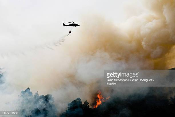 silhouette helicopter extinguishing forest fire while flying over mountain - forest fire stock pictures, royalty-free photos & images