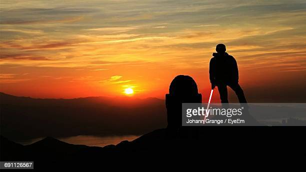 Silhouette Hiker Holding Laser Sword On Mountain Against Sky During Sunset