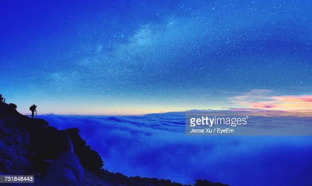 Silhouette Hiker On Mountain By Cloudscape Against Sky At Night