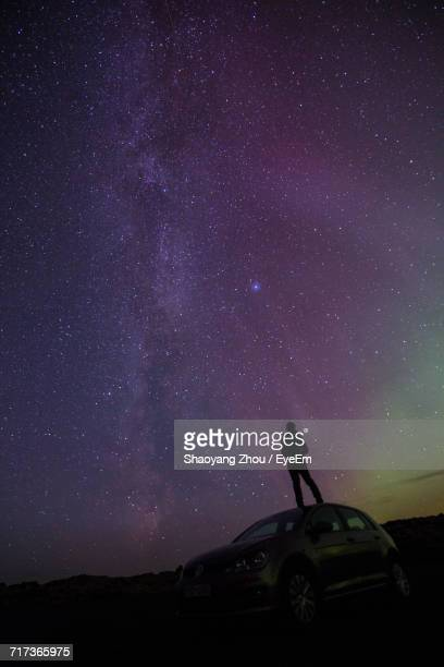 Silhouette Hiker Standing On Car Against Starry Field At Night