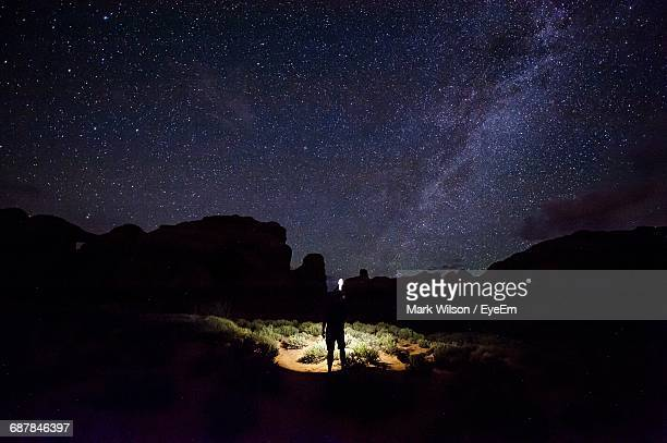 Silhouette Hiker With Flashlight Standing By Rocky Mountains Against Star Field