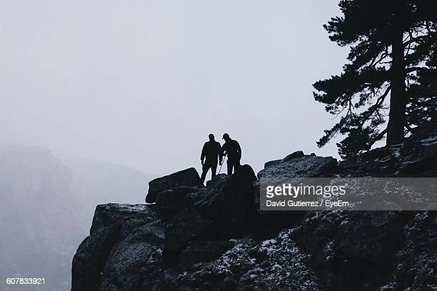 silhouette hikers on cliff against sky during foggy weather - david cliff stock pictures, royalty-free photos & images