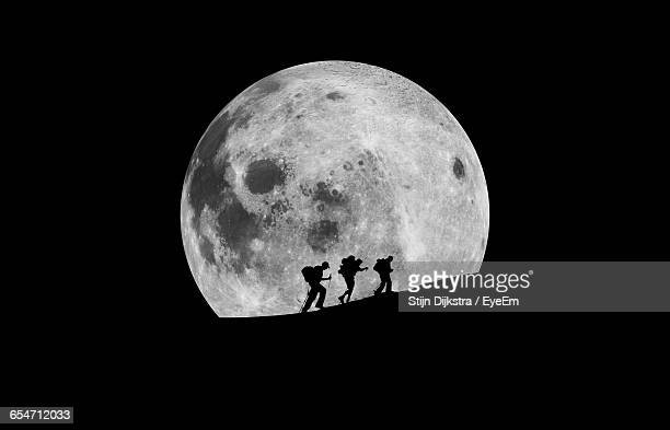Silhouette Hikers Walking Against Moon At Night
