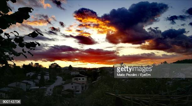 Silhouette Houses Against Dramatic Sky During Sunset