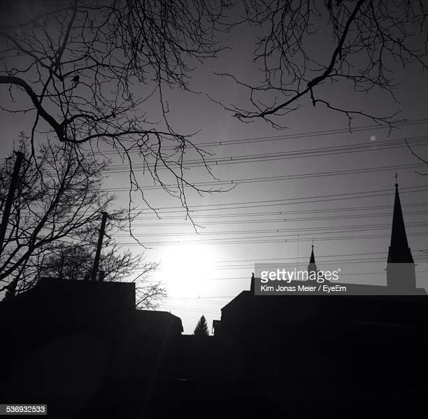 Silhouette Houses And Church With Bare Trees Against Sky
