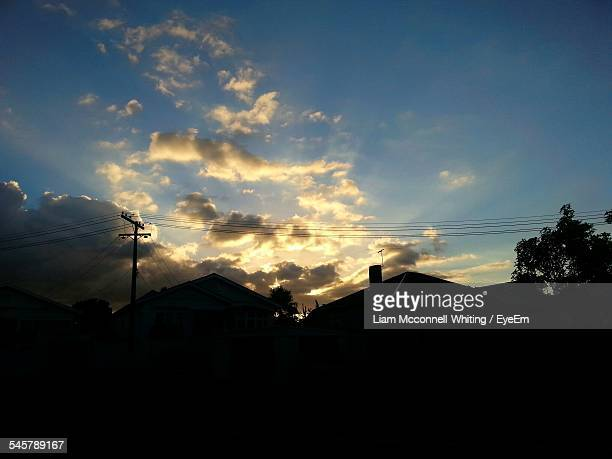 silhouette houses and electricity pylon during sunset - mcconnell stock pictures, royalty-free photos & images