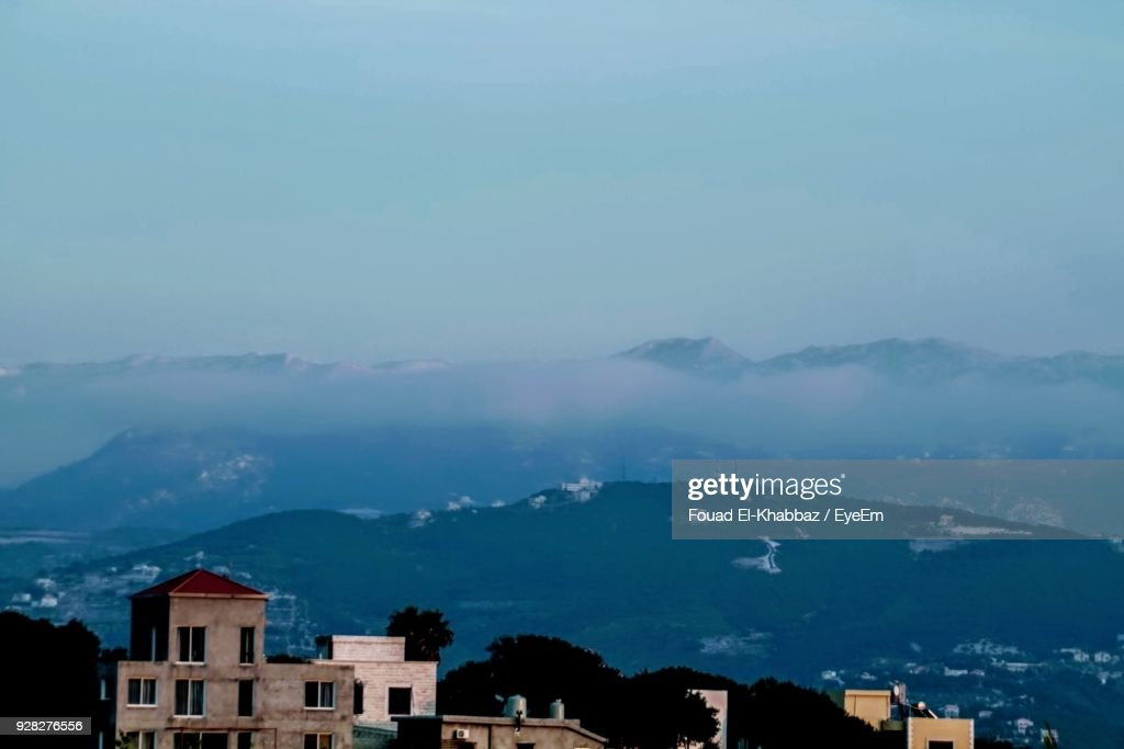 Silhouette Houses And Mountains Against Blue Sky : Stock Photo